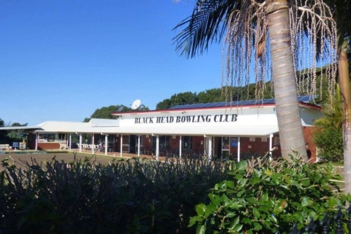 An exterior view of a bowling club, with shrubs in the foreground.