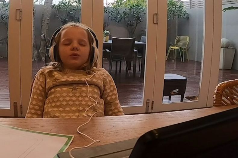 A six-year-old girl wears headphones and has her eyes closed sitting in front of a computer.