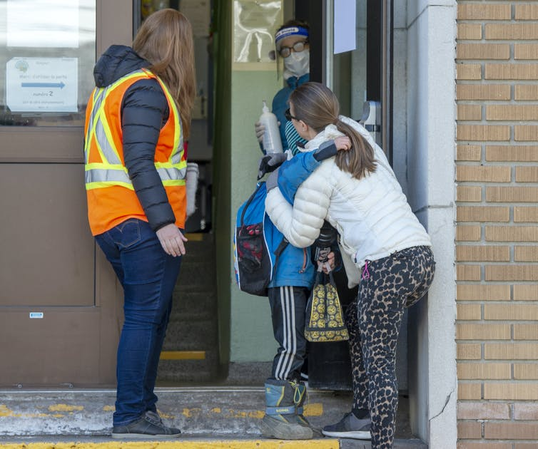 A mother and son hug as the boy makes his way into his school as a person in an orange safety vest looks on.