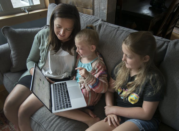 A woman and two young girls sit on a couch smiling as they look at the screen of a laptop.