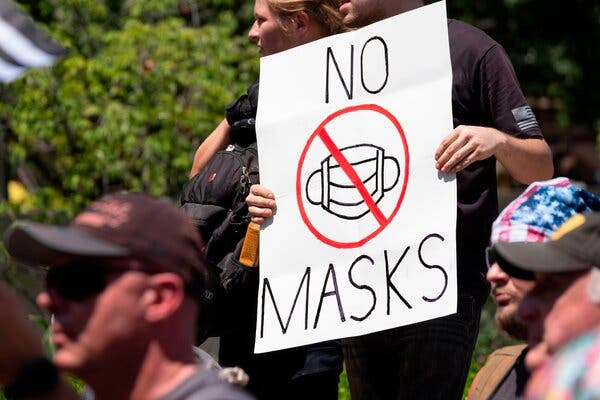"An anti-mask protestor holds up a sign in front of the Ohio Statehouse in July. Joe Biden said he could not enforce a national mask mandate everywhere, but asserted that he would have the authority to do so ""on federal land."""