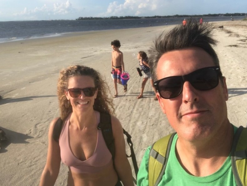 A selfie of a man in sunglasses with a blonde woman in sunglasses on the beach with two children in the background