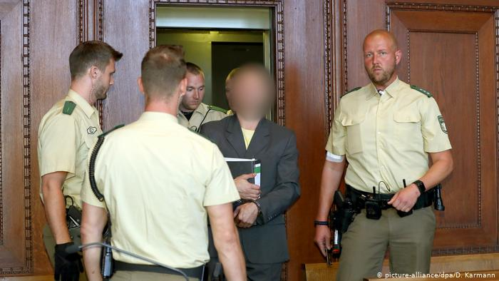 Wolfgang P., shown with face blurred, is escorted by guards in a Nuremberg courtroom