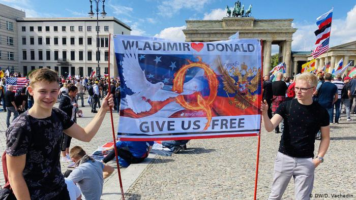 Berlin protesters holding banner asking for Donald Trump and Vladimir Putin to free Germany (DW/D. Vachedin)