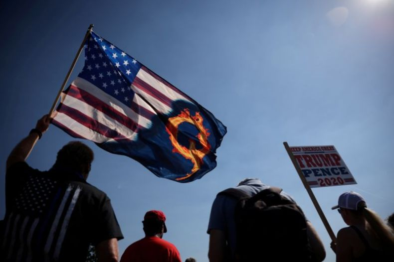 A supporter of President Donald Trump holds an U.S. flag with a reference to QAnon during a Trump 2020 Labor Day cruise rally in honor of Patriot Prayer supporter Aaron J. Danielson, who was shot dead in Portland, Oregon, after street clashes between supporters of President Donald Trump and counter-demonstrators, in Oregon city, Oregon, U.S. September 7, 2020. REUTERS/Carlos Barria