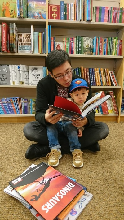 A man reads a book to his son who is sitting on his lap.