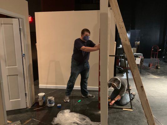 Tom Wojcik and Technical Director Cade M. Sikora set up scenery for a shoot