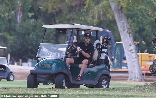 Having fun: The singer, 31, cut a casual figure in a black ensemble as he spent some downtime alone on the course