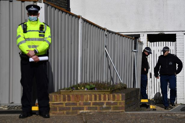 A police officer stands guard at a temporary police barrier around the home of a murder suspect in the Sarah Everard case