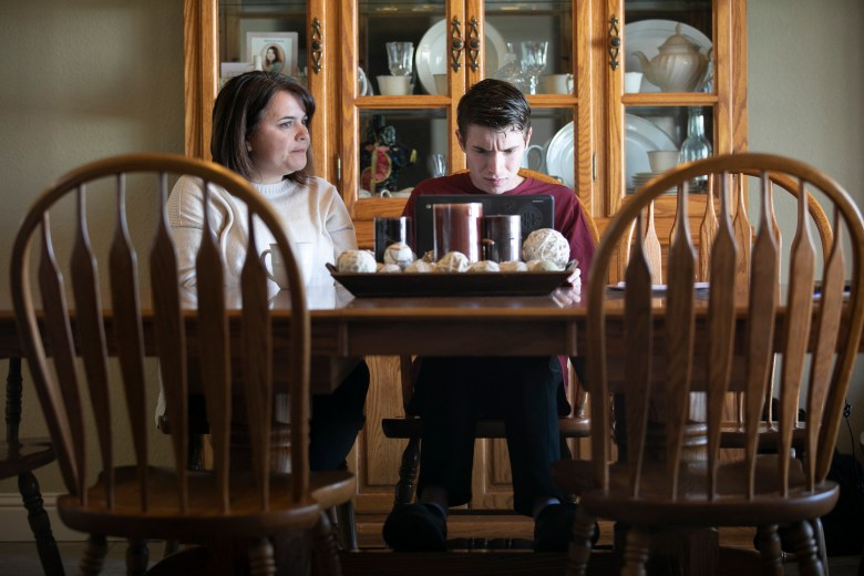 Linda Soares, left, helps her son, Daniel, 16, with his history homework at their dining room table. Soares says that she has been able to learn from her son's school aid, who is a friend, on how to best assist him with his class work. Photo by Anne Wernikoff for CalMatters