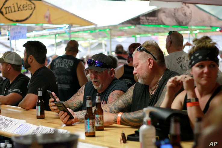 FILE - In this Aug. 7, 2020, file photo, people congregate at One-Eyed Jack's Saloon during the 80th annual Sturgis Motorcycle…