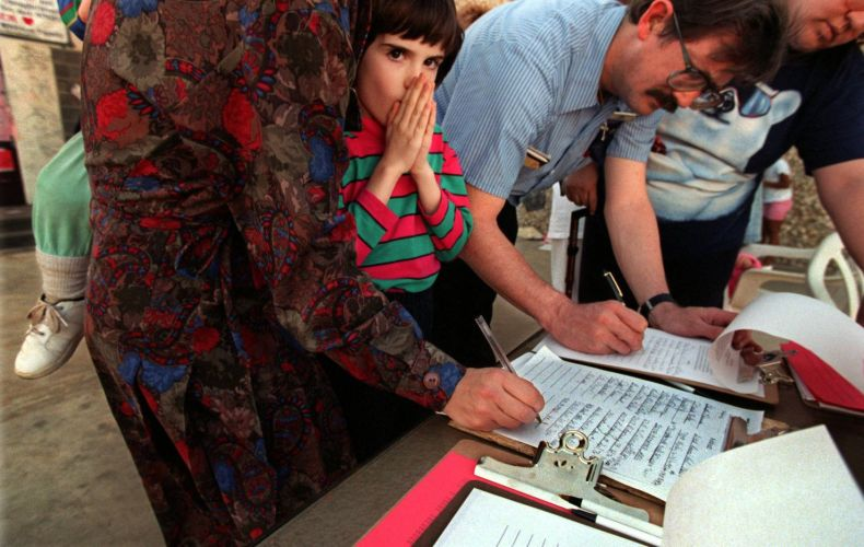 Ashley Hackney, 7, of Arlington waits while her mother, Julia, signs a petition at the site of  Amber Hagerman's abduction. At right: James Sasser, 43, of  Arlington, gets assistance from Bruce Seybert, 39, of Arlington as he signs the petition. Seybert and others spearheaded  an effort for the state to make an Amber Hagerman amendment to the Ashley Astell bill. That amendment would mandate, among  other things, a mandatory life sentence without parole for  convicted child sex offenders. Seybert said an estimated 1,000 people a day visited the site of Amber's abduction.