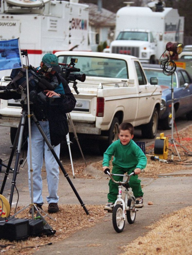 With television satelite trucks  parked outside of his grandmother's house, Richard Chad Hagerman ( 5) rides his bike under the watchful eye of a television camera.  Richard's sister, Amber Hagerman was abducted as the two rode  bicycles in the neighborhood.