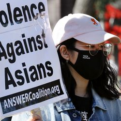 A woman who asked not to be named holds a sign during a protest against anti-Asian racist violence, violence against women and white supremacy at the International Peace Gardens in Salt Lake City on Saturday, March 27, 2021.