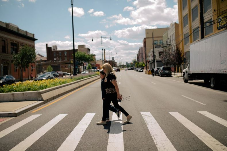 Milagros Reyes and her son José walk home from school across the long white lines of a crosswalk on a bright June day.