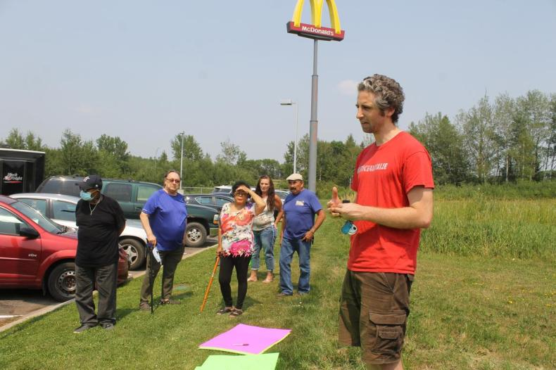 David Boehnke of End MSOP, talks to the family members and fellow protesters in the parking lot of a McDonald's near the Minnesota Sexual Offenders Program facility in Moose Lake. (Teri Cadeau / tcadeau@duluthnews.com)