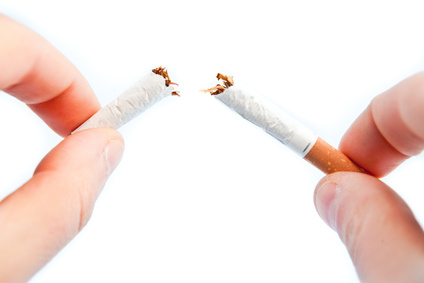 Fingers breaking a cigarette against a white background