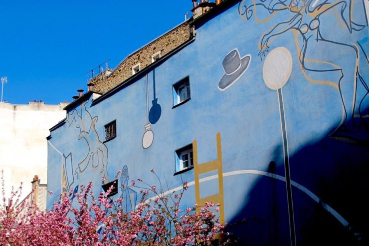 A mural somewhere around Montmartre, with cherry blossoms in the foreground. Image credit: Courtney Traub/All rights reserved.