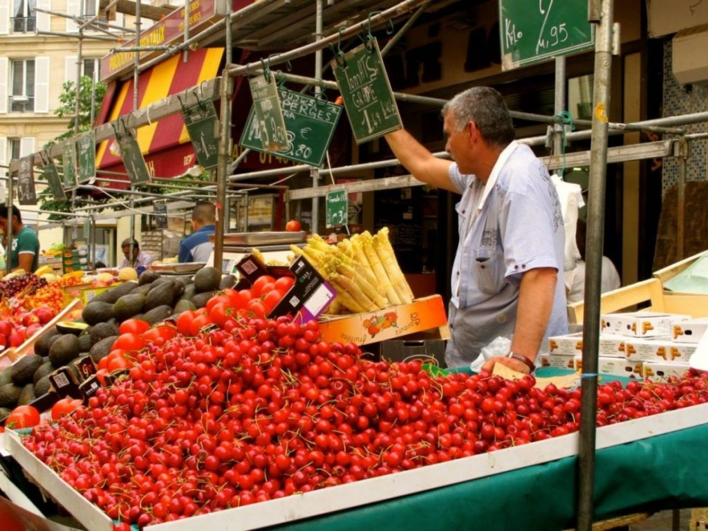 A vendor offers heaps of cherries and other fresh produce at the Marche d'Aligre, one of Paris' loveliest open-air markets. Image: Courtney Traub