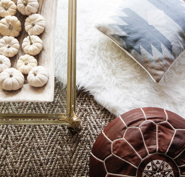 living room styling with coffee table, pouf, and pillow