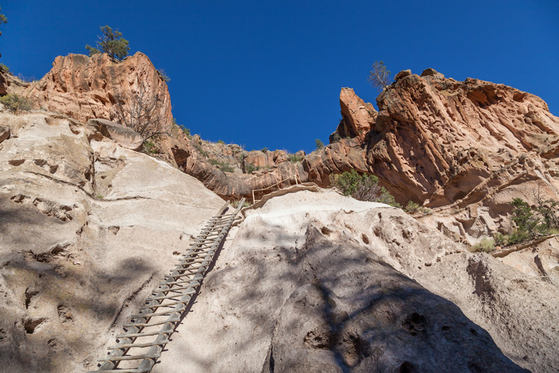 hiking up a ladder in bandelier national park in new mexico