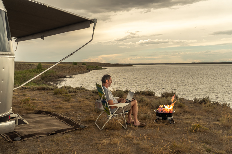 portable fire pit on a beach next to an airstream RV motorhome
