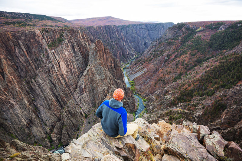 sitting on the edge of black canyon of the gunnison national park in colorado