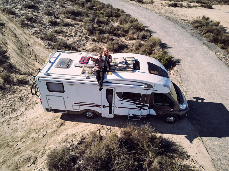 couple sitting on a camper roof
