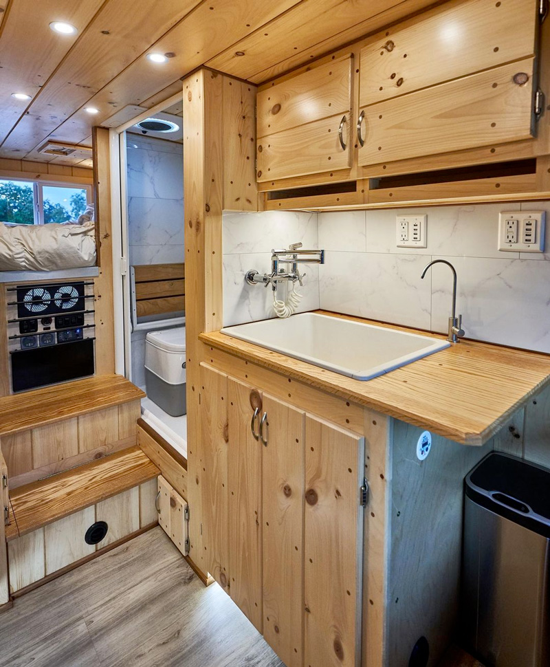 camper van with shower and bathroom sink and toilet installed