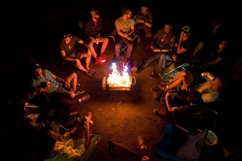 group of friends sitting around a portable campfire at a camping site