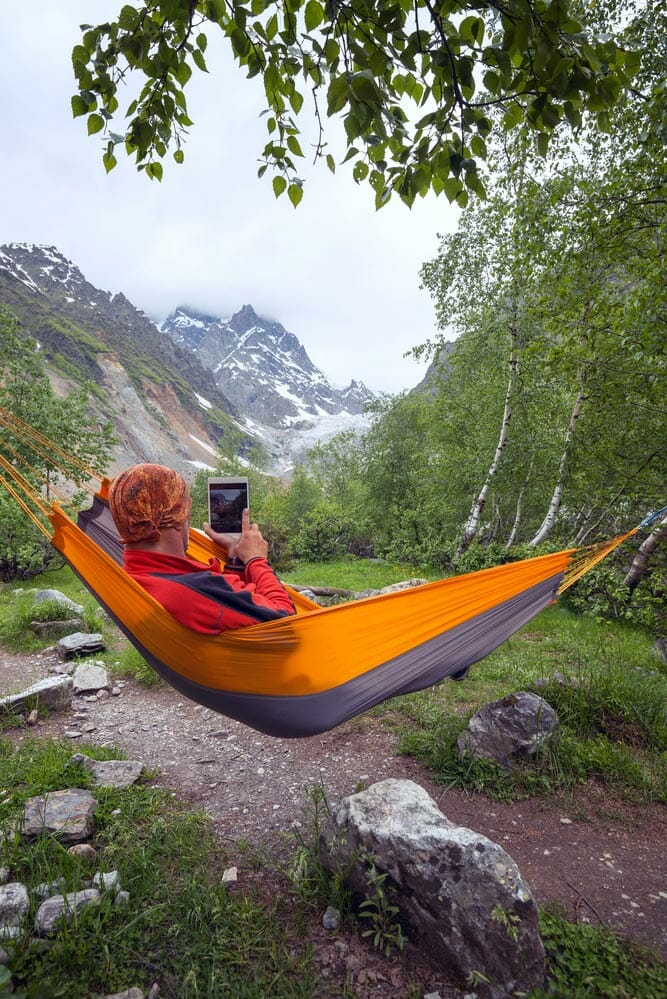 hanging a portable hammock while camping in the mountains