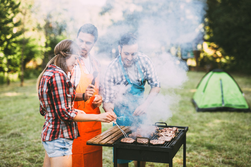 cooking on a portable grill at a camping site