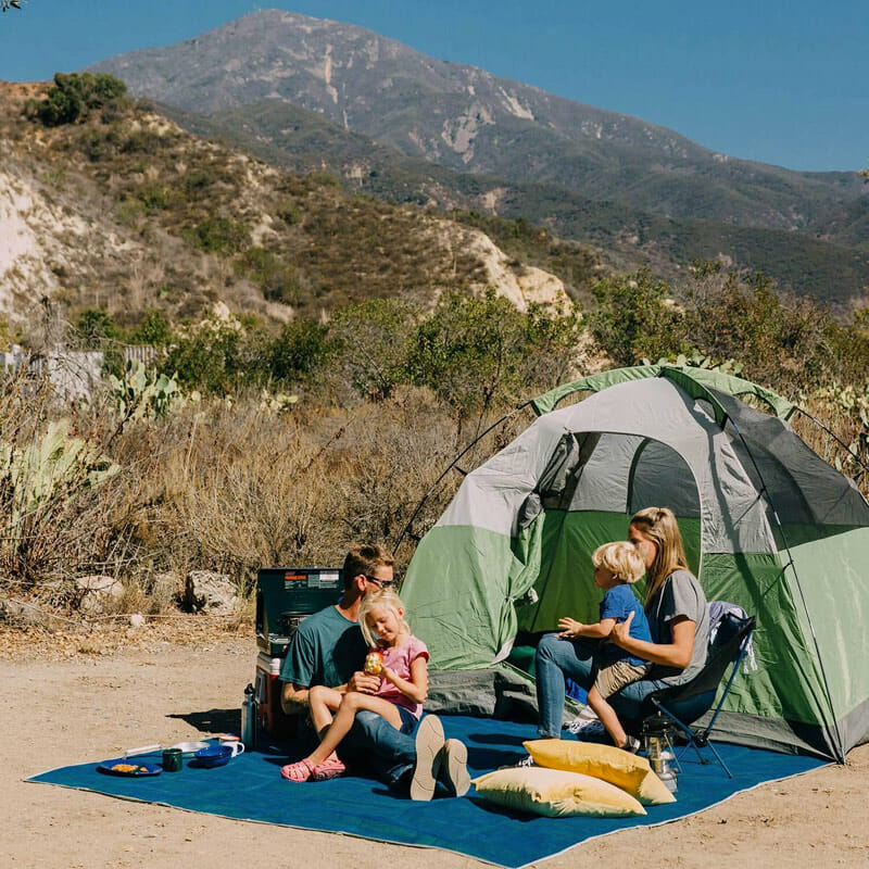 family tent camping with a sand free rug