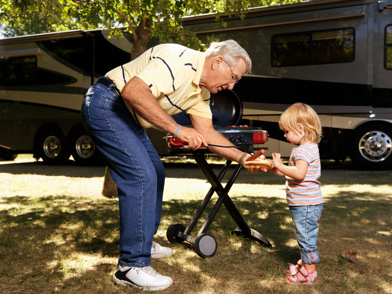 grilling a hot dog on a portable propane grill in front of an rv