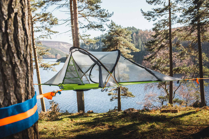 camping tent hanging between three trees
