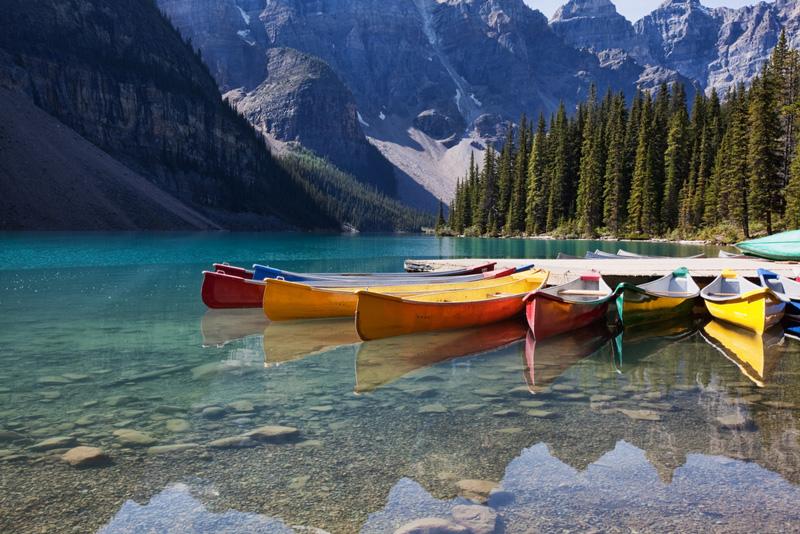 canoe vs kayaks sitting on a lake