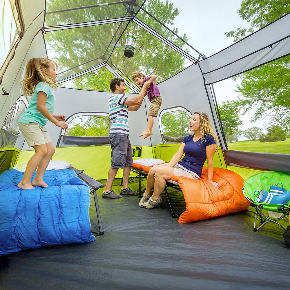 Large camping tent with family playing inside