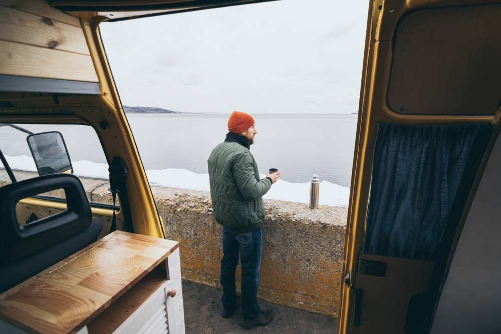 man drinking a cup of coffee outside of a camper van conversion