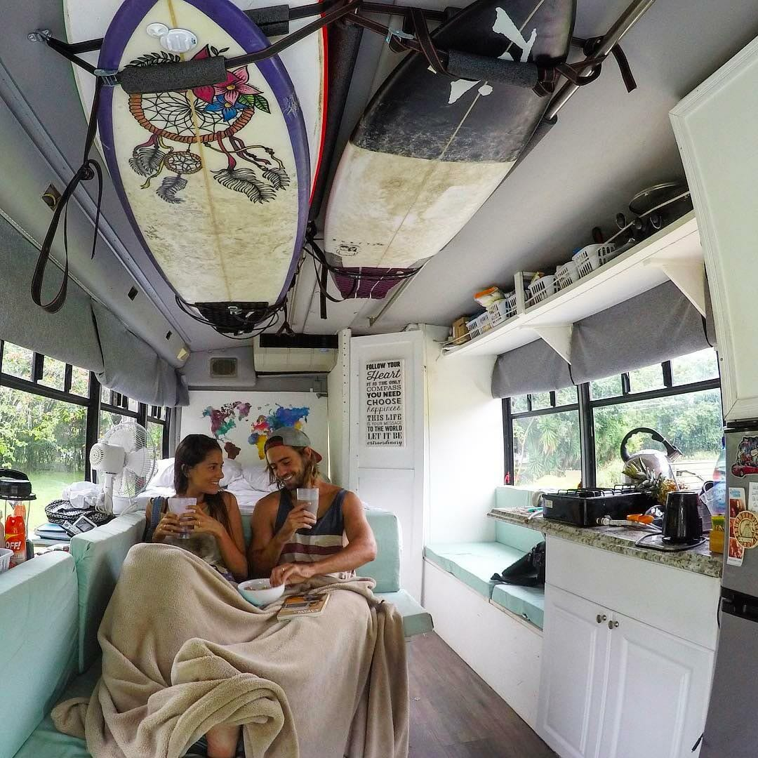Surfing couple in a school bus conversion