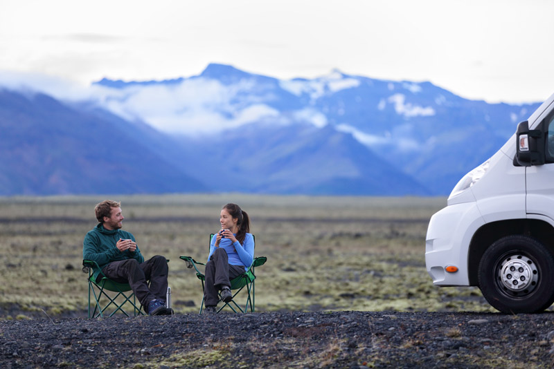 couple sharing a cup of coffee outside of their motorhome or travel trailer in the mountains