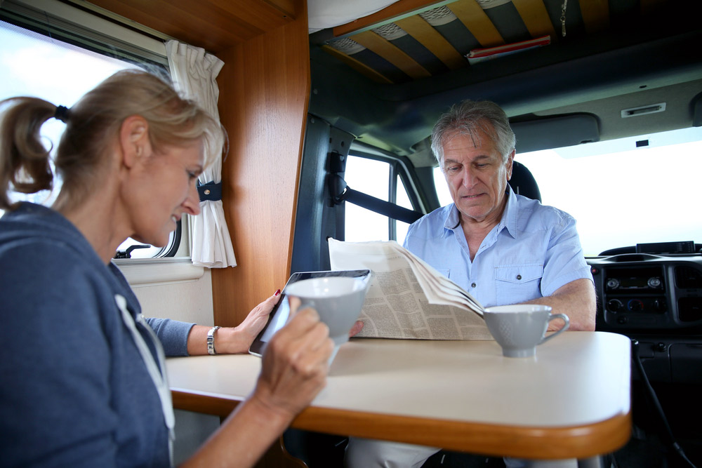 older travel couple drinking coffee brewed from an rv coffee maker