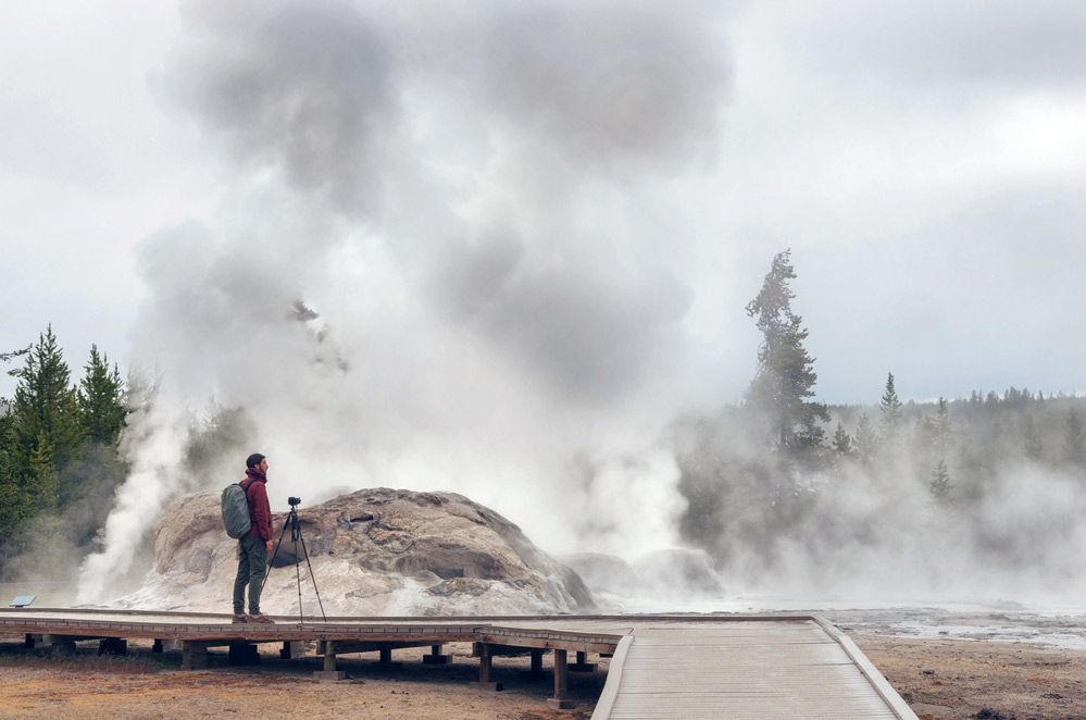 photographer taking picture of a geyser eruption and other things in yellowstone national park