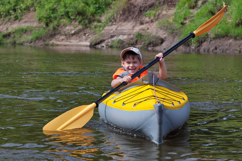 young child kayaking in a lake