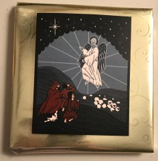 An angel greets shepherds in muted teal and burgundy and white toned scene