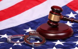 Judge Gavel and Handcuffs over American Flag