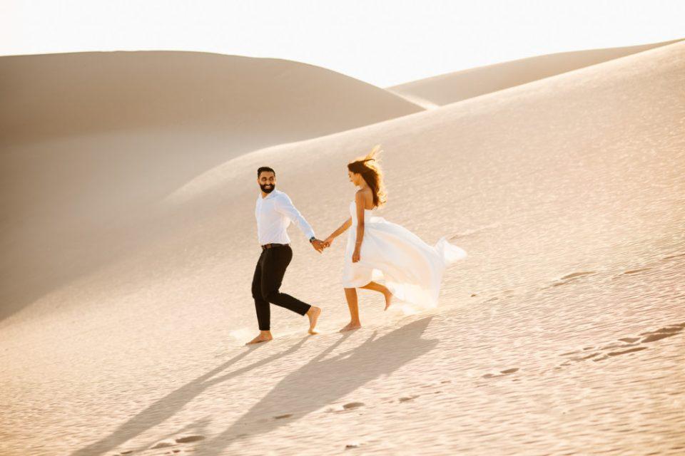 Sand dunes engagement couple running