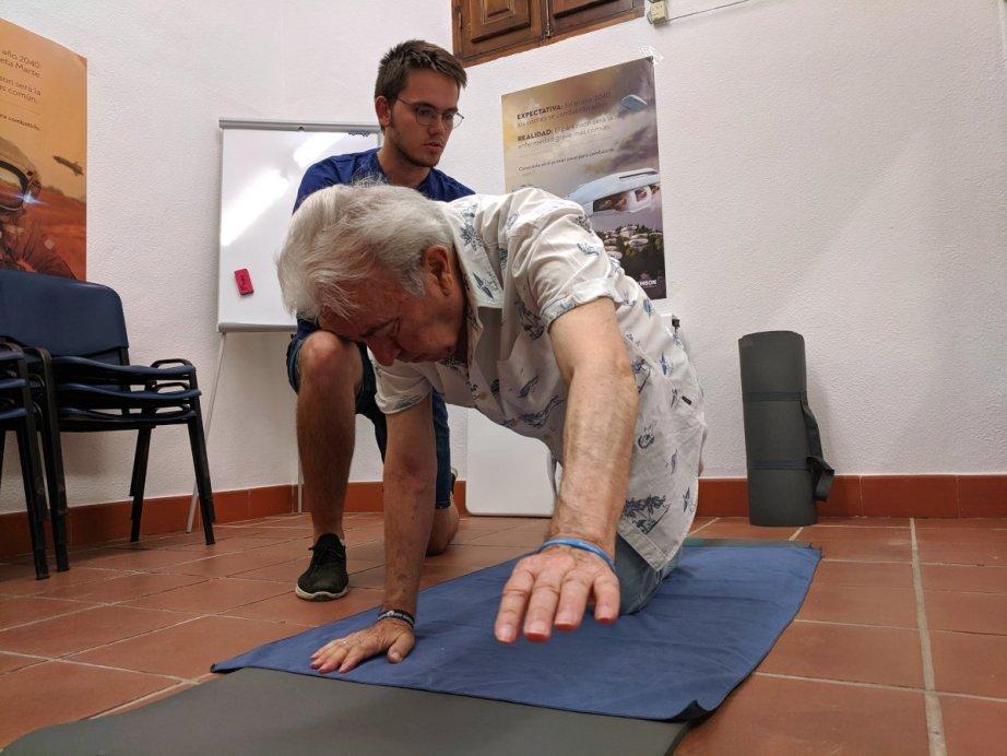 Terapeuta y paciente haciendo ejercicios sobre colchoneta, parte de los ejercicios para corregir la postura en la enfermedad de párkinson