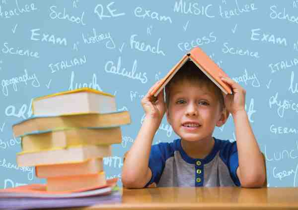 Boy with book on head against school doodle background