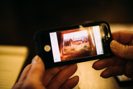 Pat's cell phone displays a snapshot of his original homestead cabin, circa 1950s