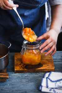 Home canning ham. Housewife filling peach, melon, pineapple and apricot jam into a glass. Rustic blue style.